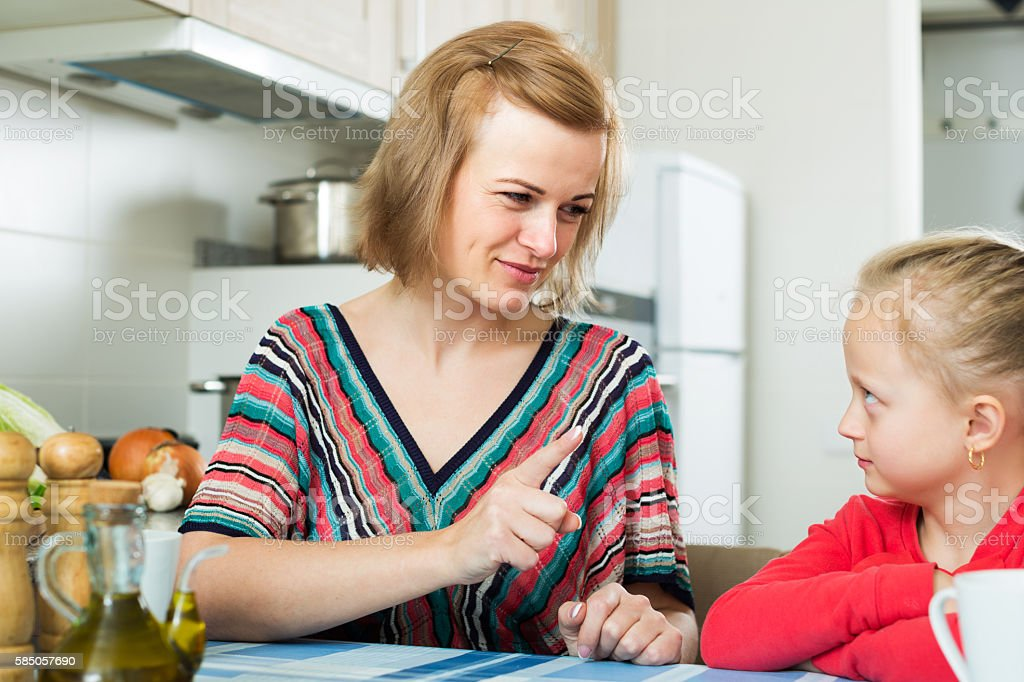 Upset mother shaming daughter stock photo