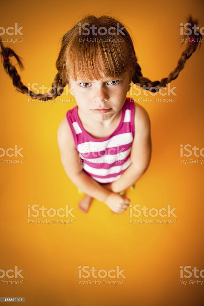 'Upset, Red-Haired Girl with Upward Braids and a Scowl' stock photo