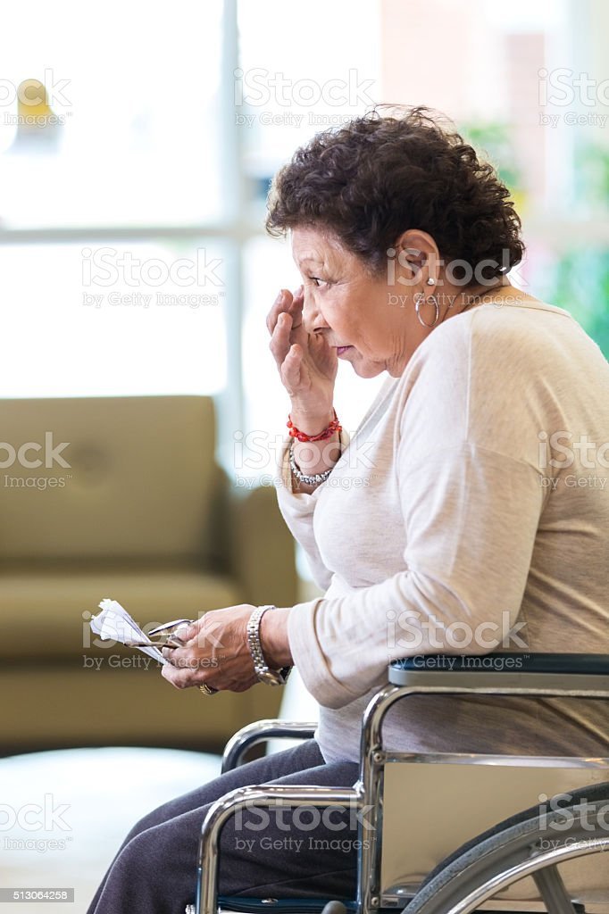 Upset senior woman in wheelchair in nursing home stock photo