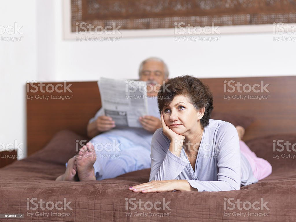 Upset senior woman lying down in bed royalty-free stock photo