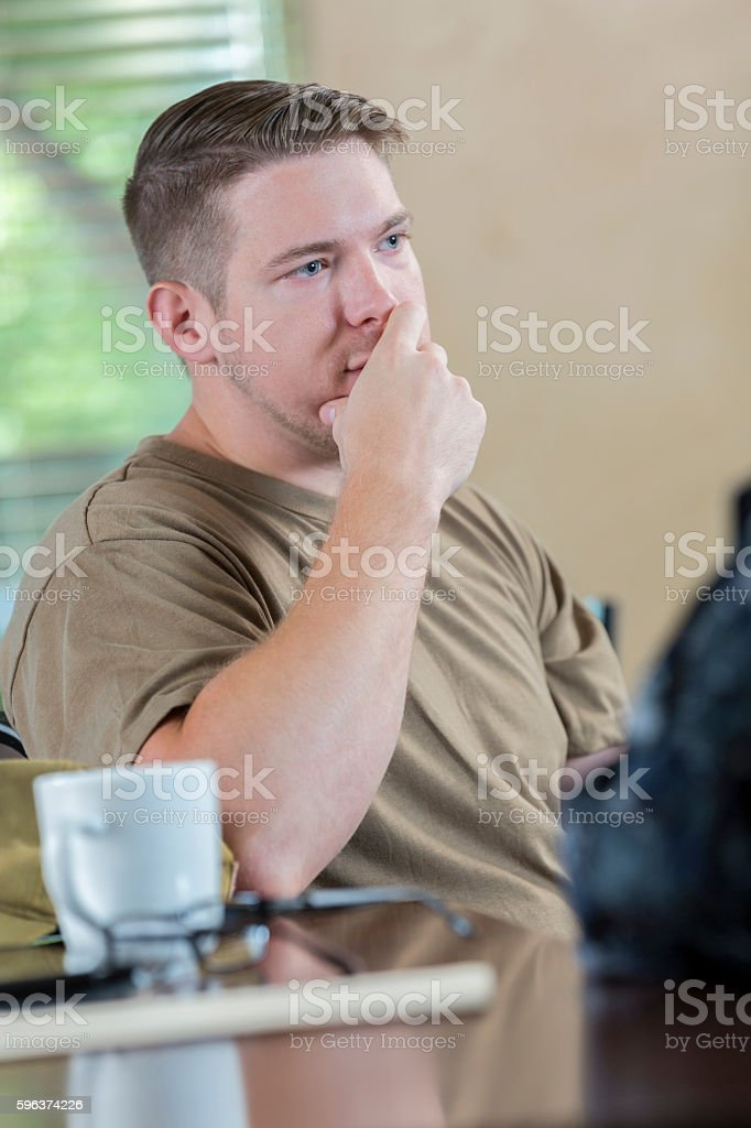 Upset soldier being evaluated by military counselor or doctor stock photo
