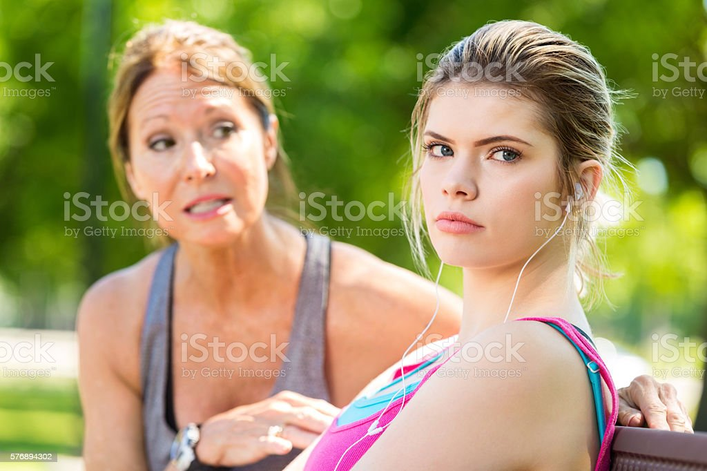 Upset teenage daughter ignoring her concerned mother during an argument stock photo
