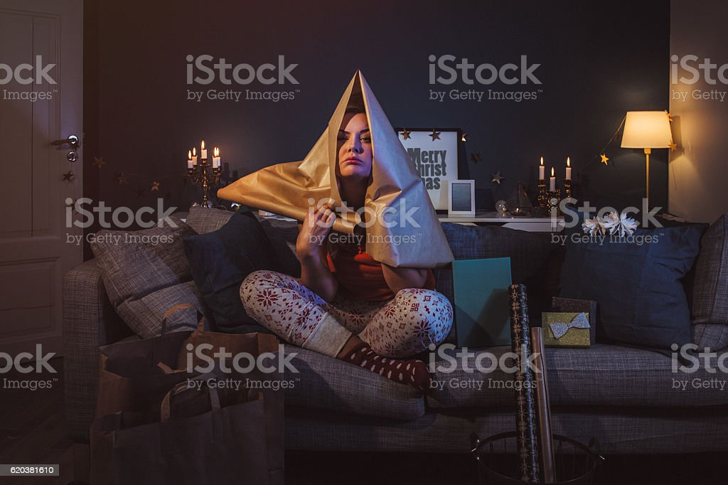 Upset woman at home with christmas gifts stock photo