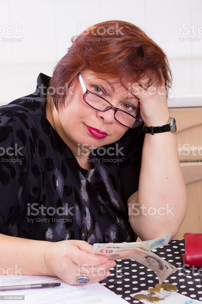 Upset woman counting money to pay bills stock photo