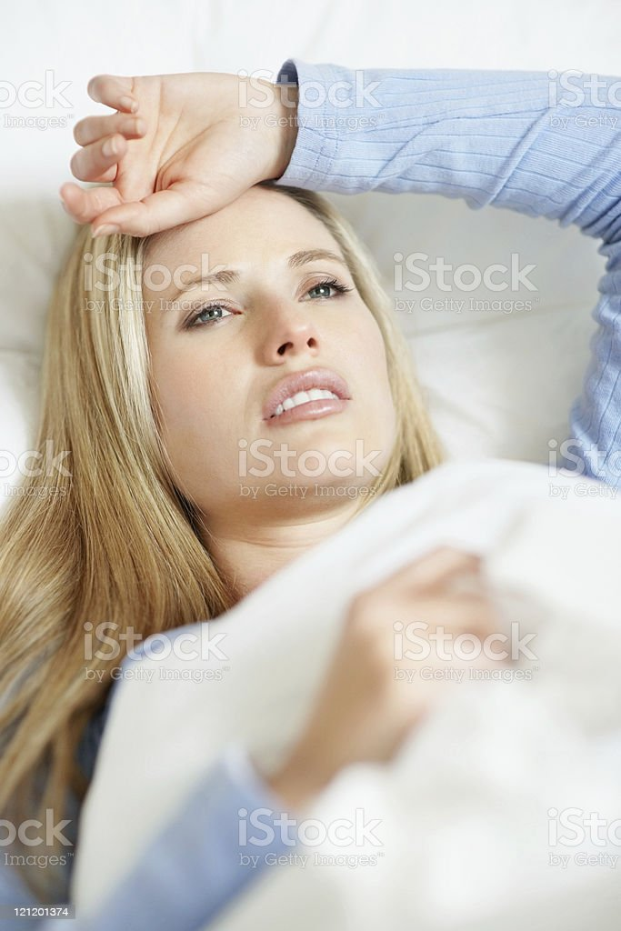 Upset woman having a migraine lying on bed at home royalty-free stock photo