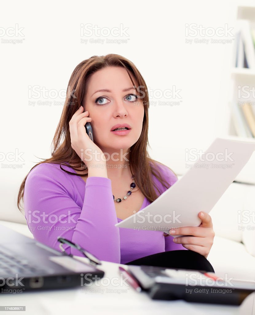 Upset woman holding papers talking on the telephone royalty-free stock photo