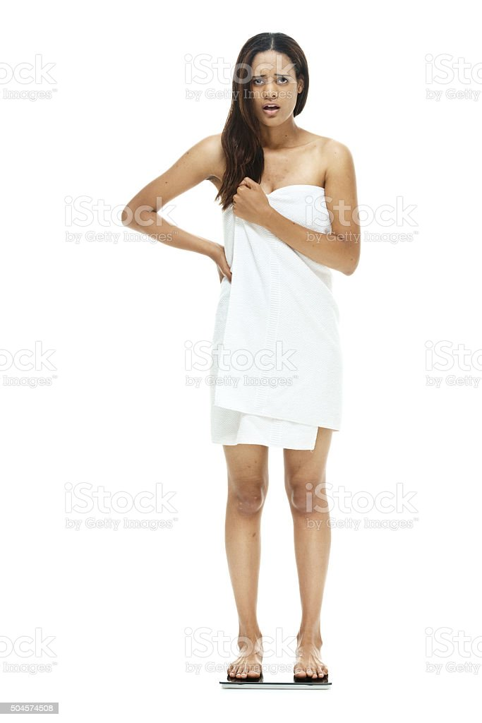 Upset woman measuring her weight stock photo