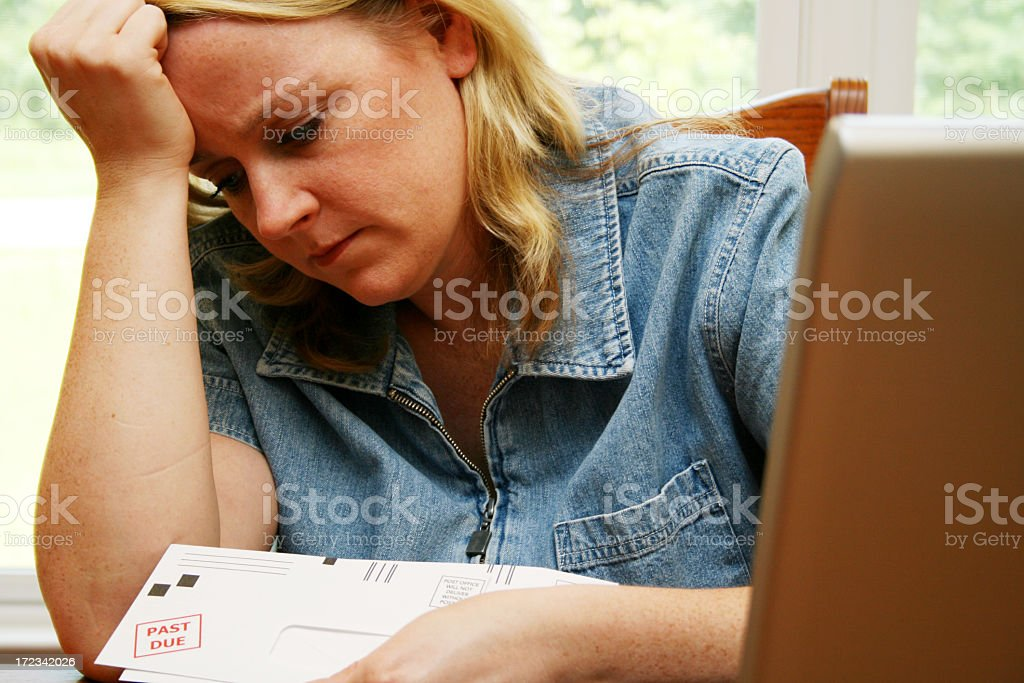 Upset woman paying past due bills stock photo