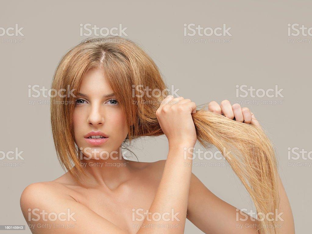 upset woman pulling dry hair split ends stock photo