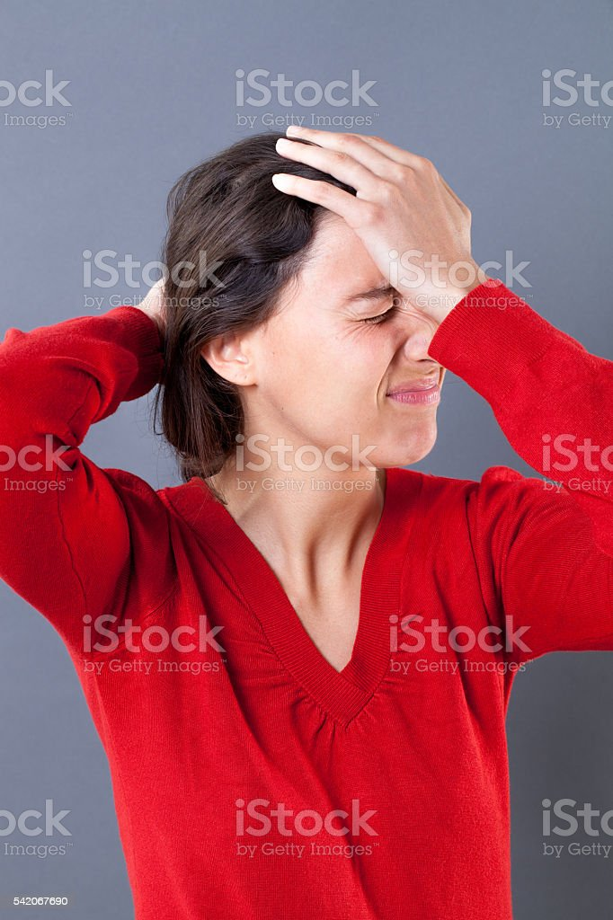 upset woman with eyes closed touching her forehead for regret stock photo