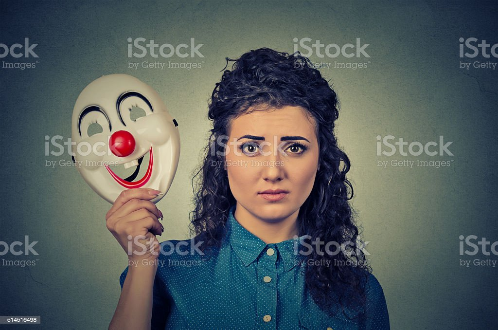 upset woman with sad expression holding clown mask stock photo