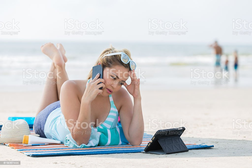 Upset woman with smart phone on a beach vacation stock photo