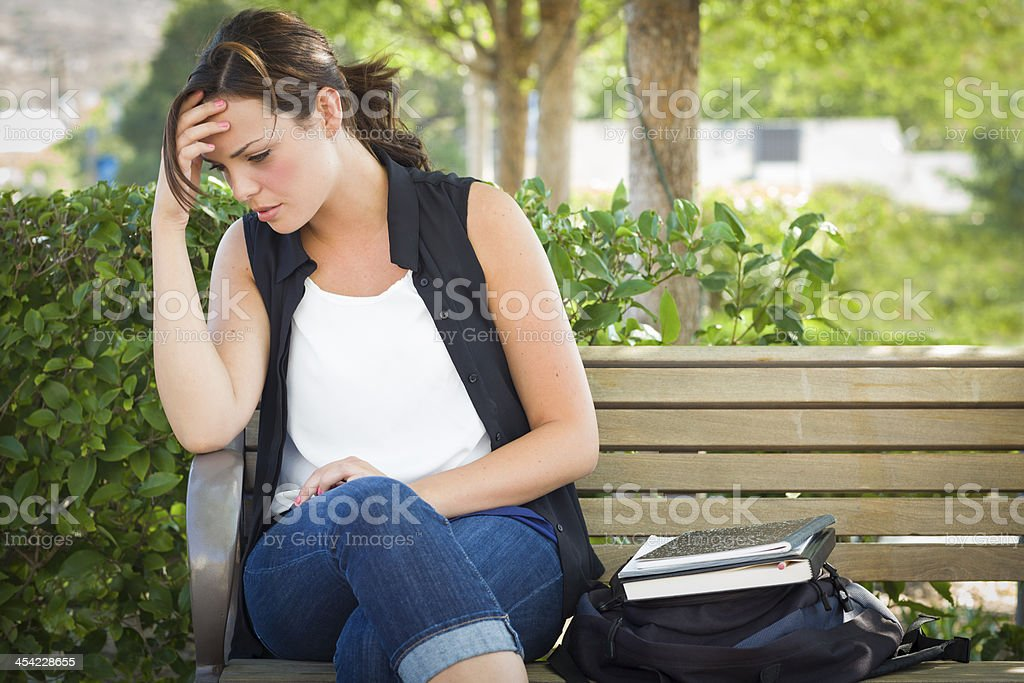 Upset Young Woman Sitting Alone on Bench Next to Books stock photo