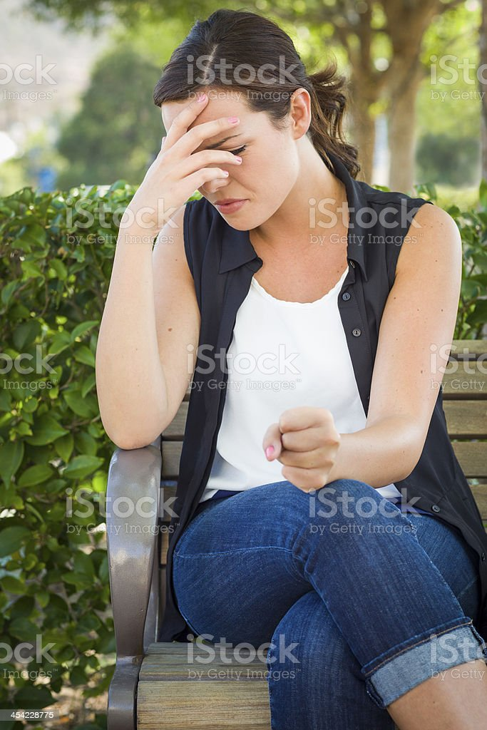 Upset Young Woman Sitting Alone on Bench stock photo