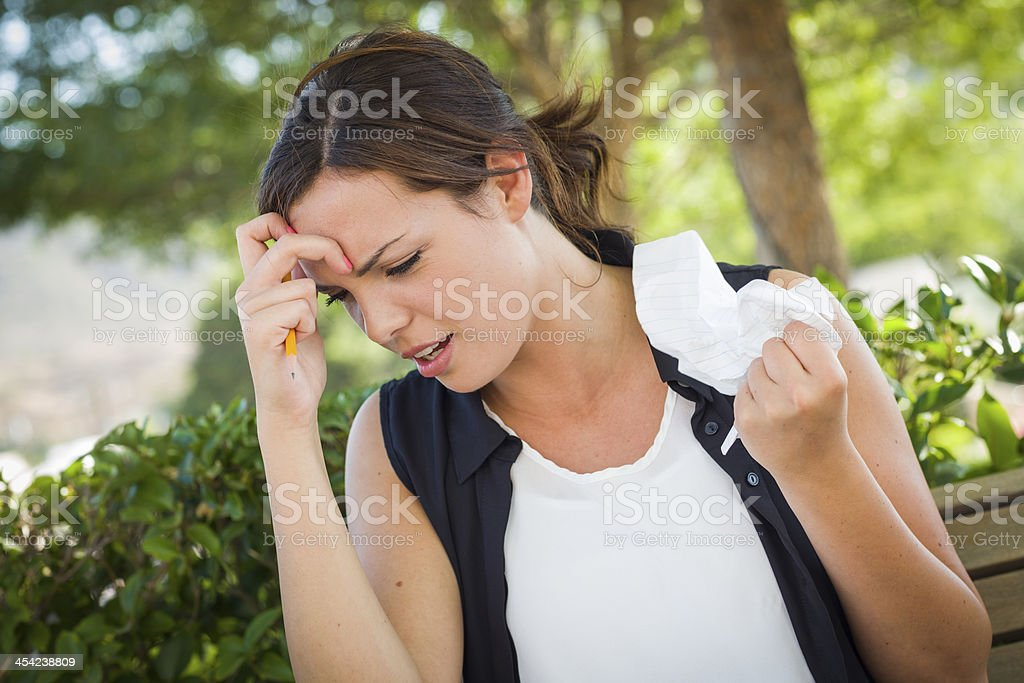 Upset Young Woman with Pencil and Crumpled Paper in Hand royalty-free stock photo
