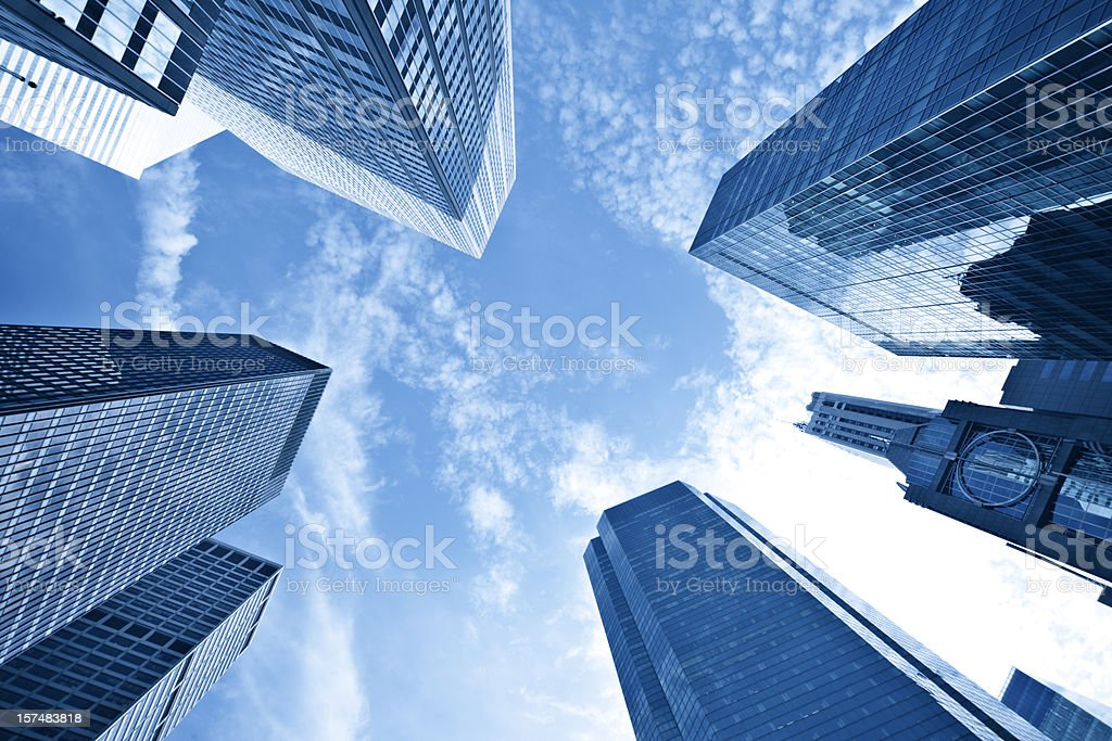 Upshot of tall skyscrapers against blue sky and wispy cloud stock photo