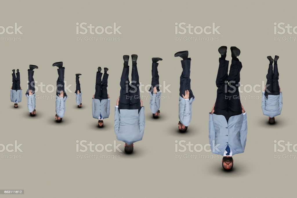 Upside down businessmen in light-blue suits. stock photo