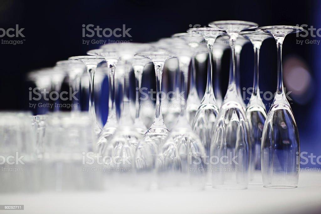 Upturned set of wine glasses on blurred blue background stock photo