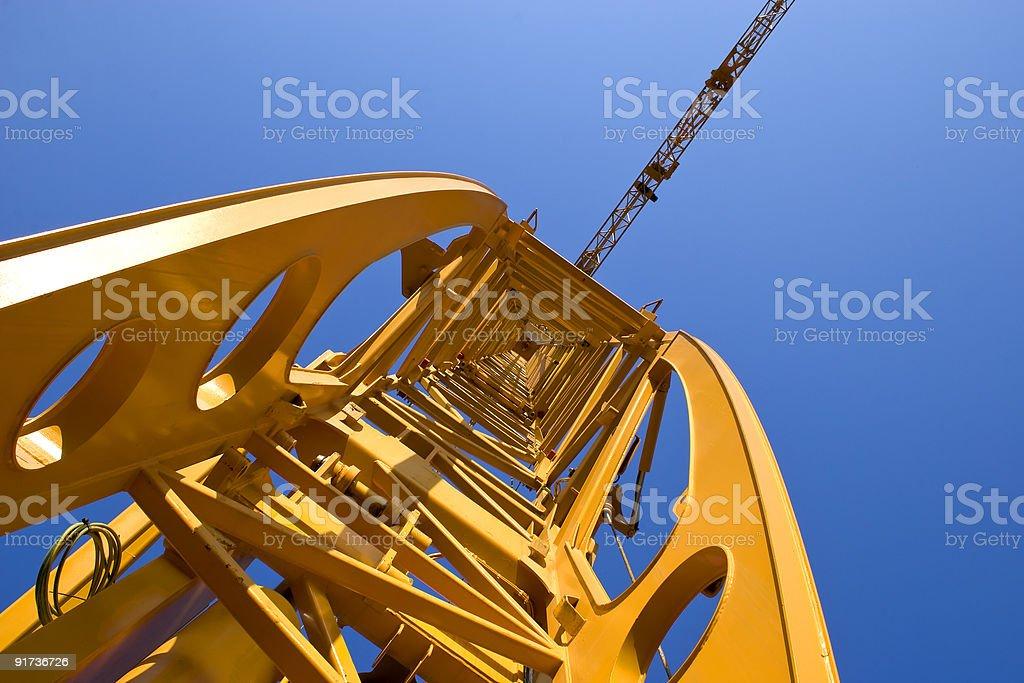 Upward shot of orange construction crane from inside stock photo