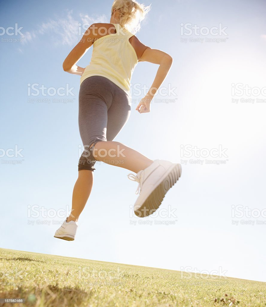 Upward view of a female athlete running on field royalty-free stock photo
