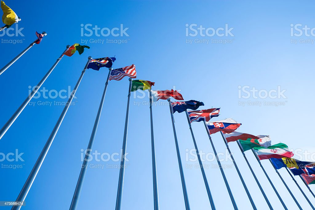 Upward view of flags from different countries stock photo