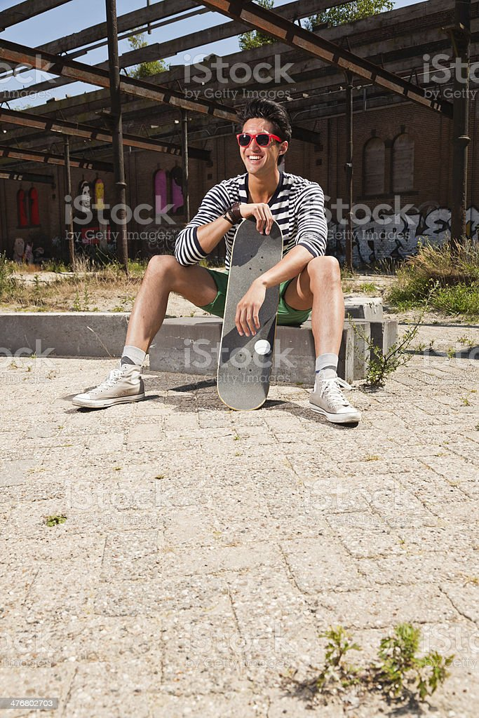 Urban asian man with red sunglasses and skateboard. royalty-free stock photo