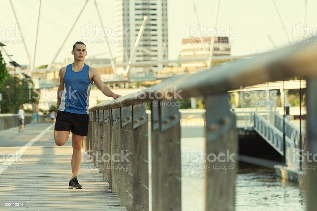 Urban athlete stretching his legs stock photo