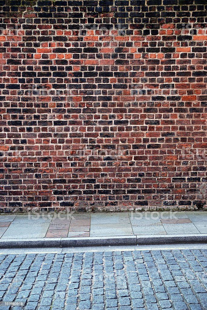 Urban background UK - Red brick wall with sidewalk royalty-free stock photo