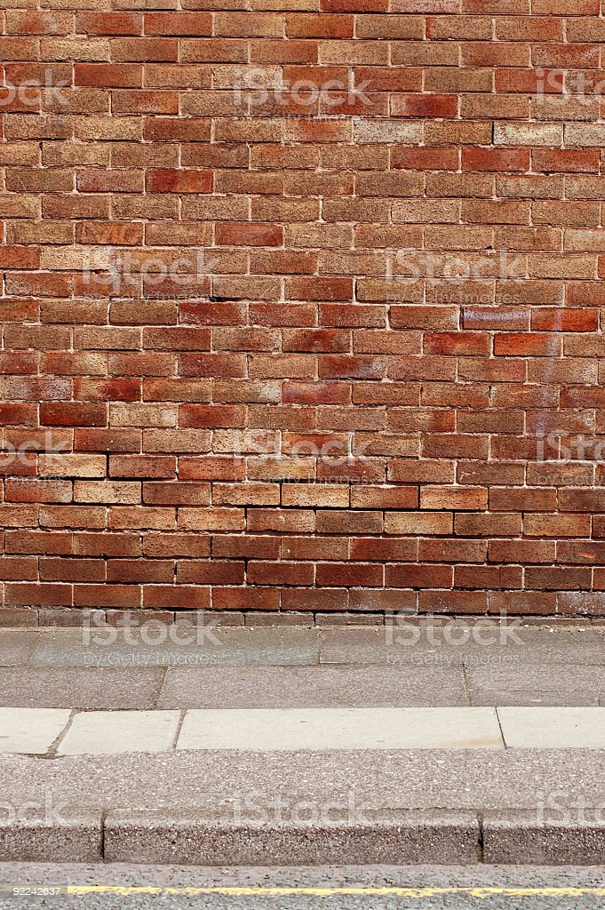 Urban background UK - Red brick wall with sidewalk royalty-free stock photo
