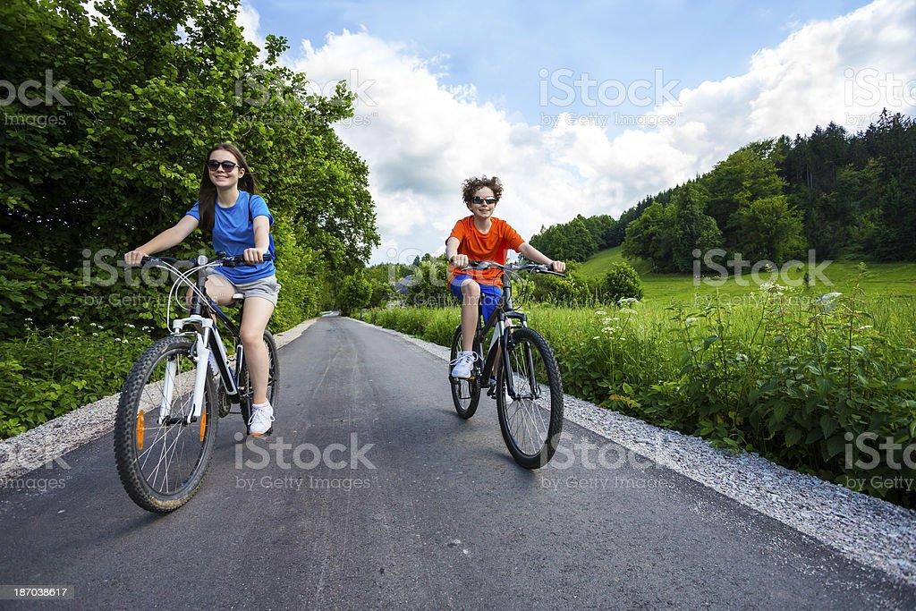 Urban biking- girl and boy riding bikes in city park royalty-free stock photo