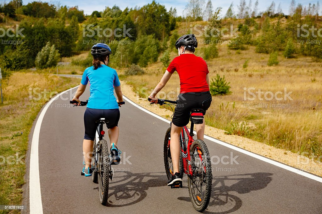 Urban biking- girl and boy riding bikes in city stock photo