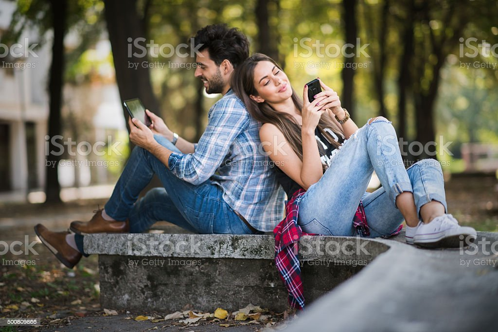 Urban couple in the park sitting back to back stock photo