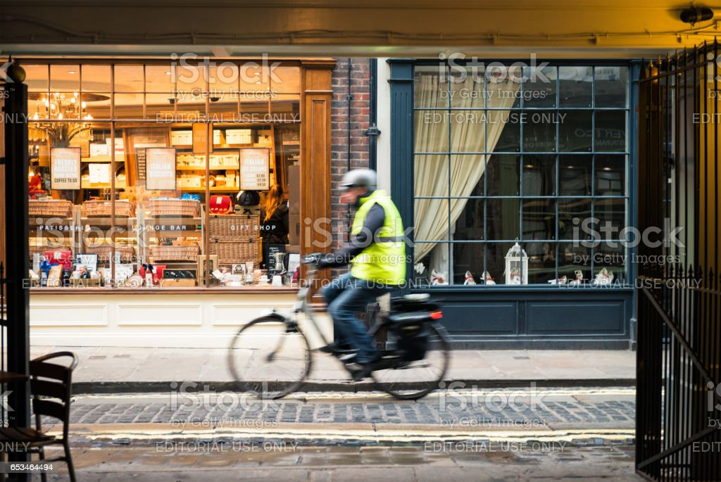 Urban cyclist passing shops - motion blur stock photo
