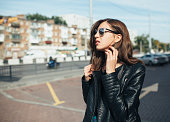Urban fashionable girl posing in a leather jacket outdoors in