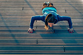 Urban fitness. Woman doing push-ups on outdoor stair