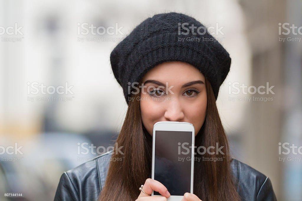Urban girl holding a cellphone. stock photo
