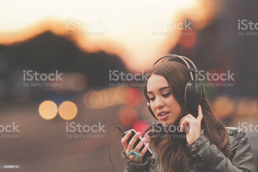 Urban girl listening to some music. stock photo