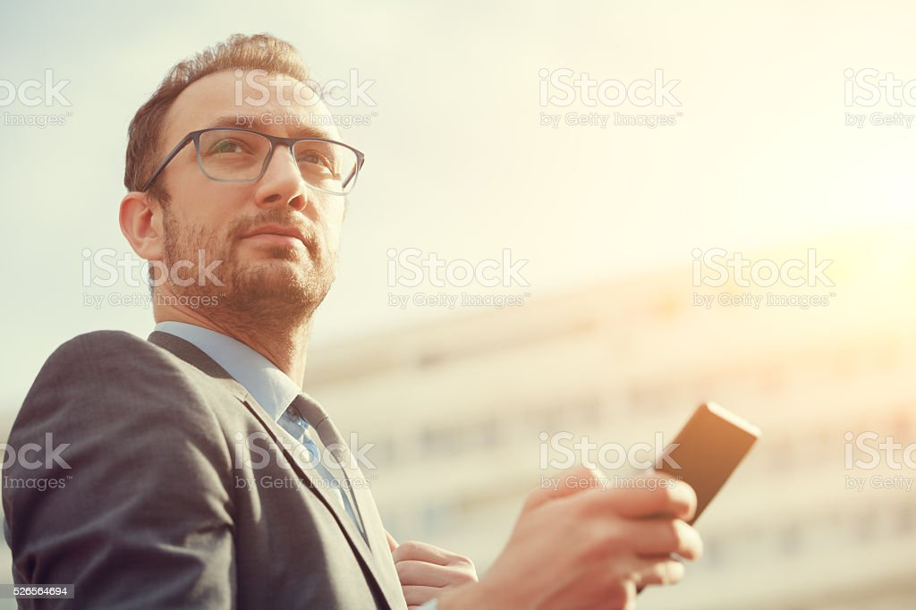 Urban guy / businessman with a cellphone outdoors. stock photo