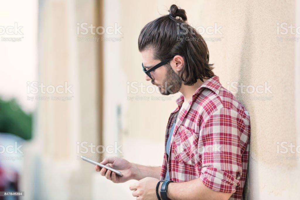 Urban guy using cellphone on the street. stock photo