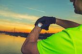 Urban jogger checking his running time.
