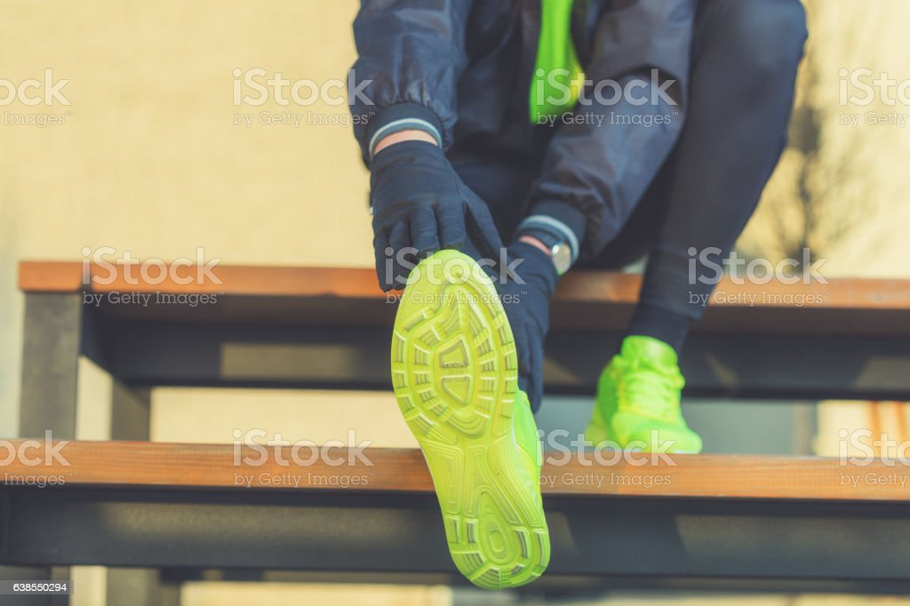 Urban jogger stretching on the bench. stock photo