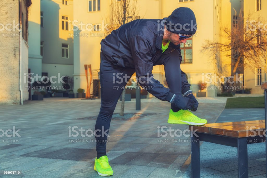 Urban jogger tying running shoes in the park. stock photo