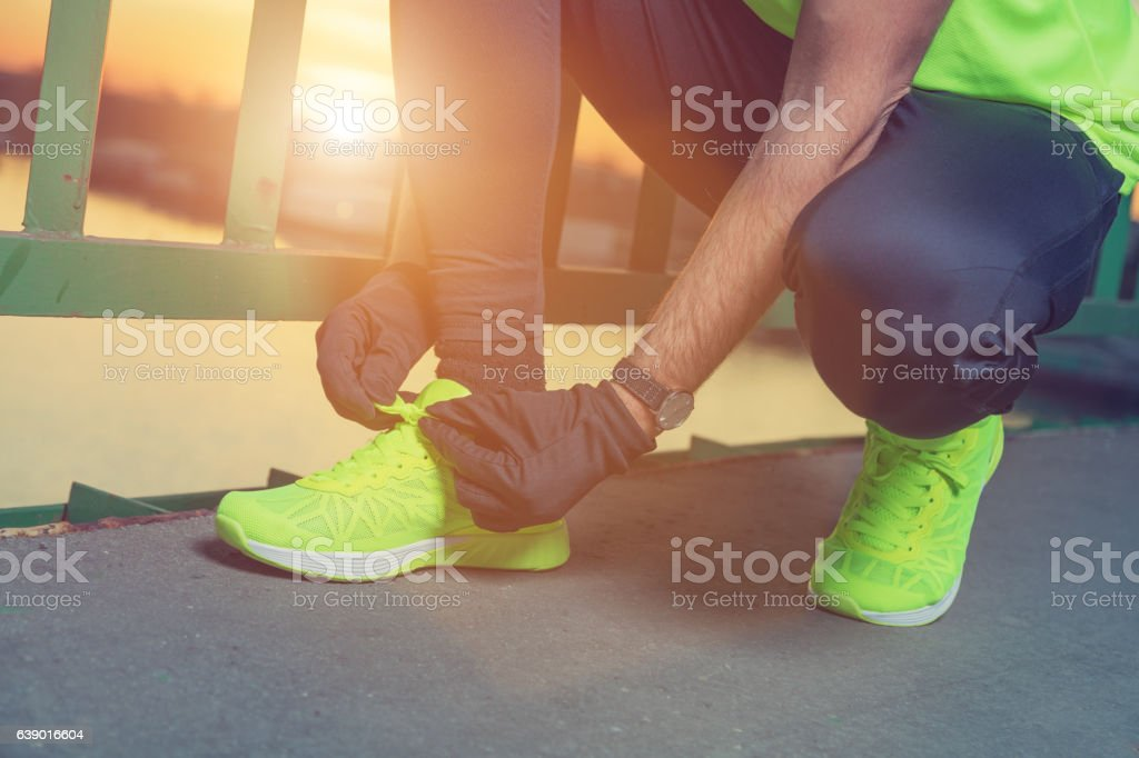 Urban jogger tying running shoes on the bridge. stock photo
