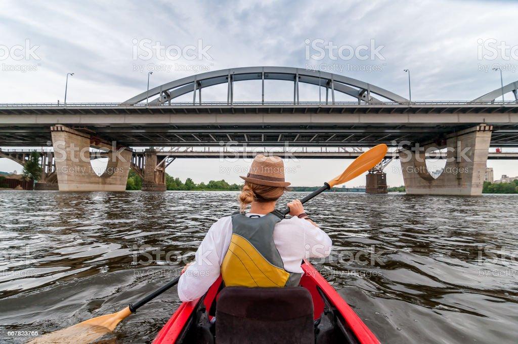 Urban kayaking travel by the river. Beautiful young girl at red kayak...