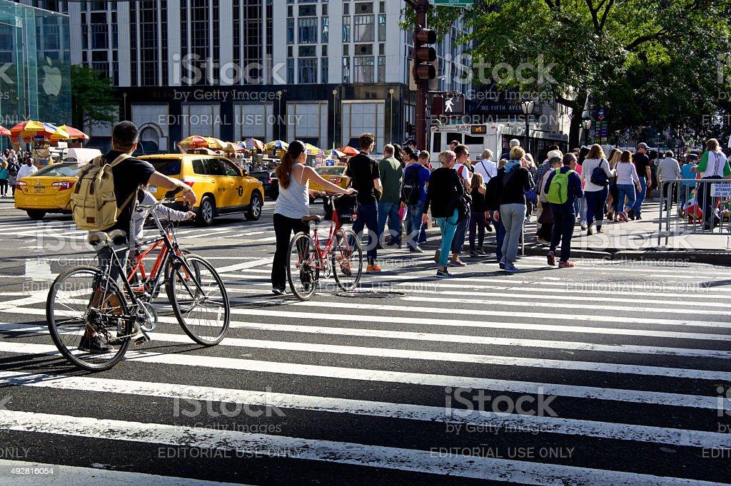 Urban Life, New York City, Bicyclists Walking across Manhattan Intersection stock photo