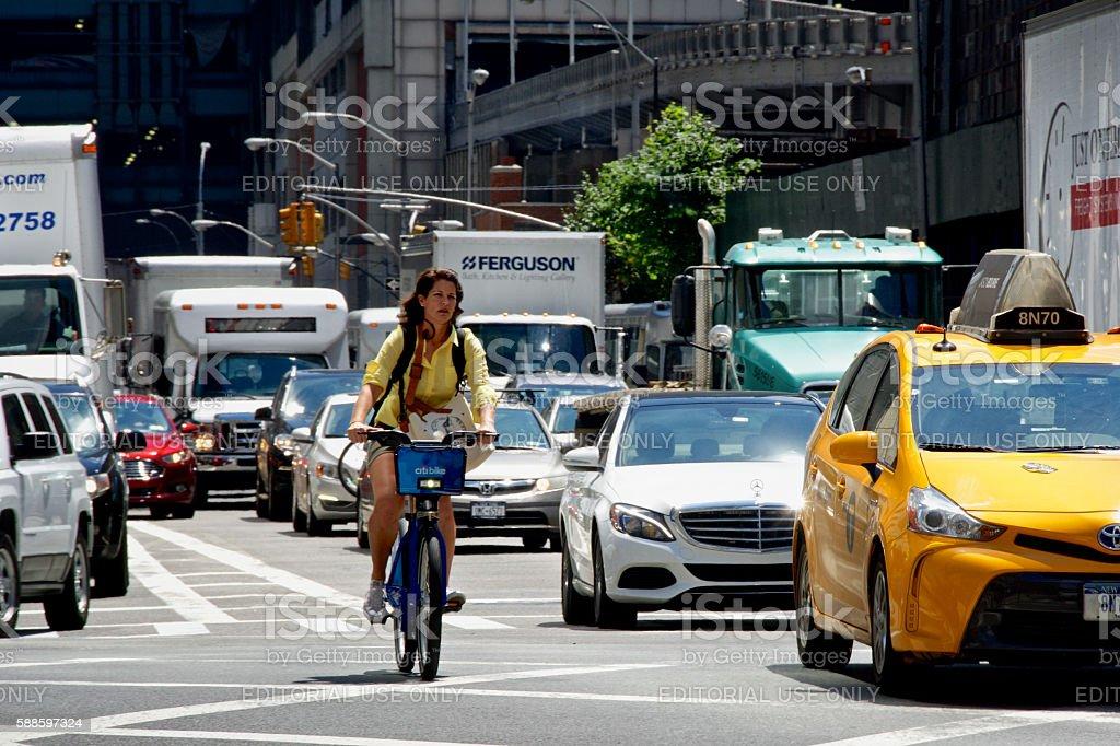 Urban Life, New York City, Female Bicyclist Passing Vehicles, Manhattan stock photo