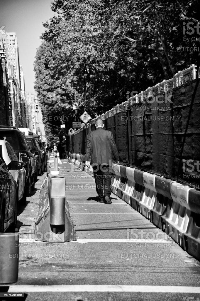 Urban Life, New York City. Male pedestrian walking past construction barriers, Central Park West, Manhattan stock photo