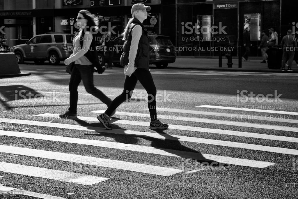 Urban Life, New York City Pedestrians. Two Women Passing in opposite directions in crosswalk, Upper West Side, Manhattan stock photo