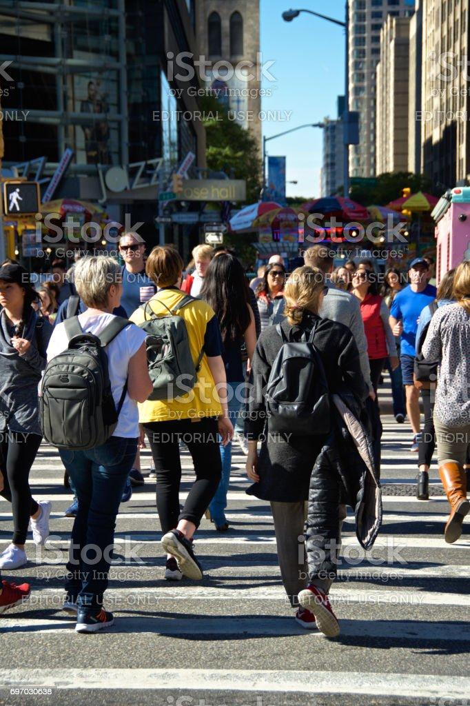 Urban Life, New York City. Pedestrians walking  across Central Park West at Columbus Circle, Manhattan. stock photo