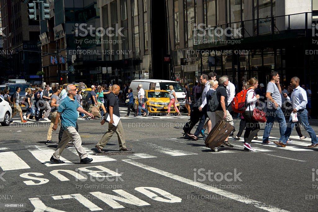 Urban Life, New York City, Pedestrians Walking across Manhattan Intersection stock photo